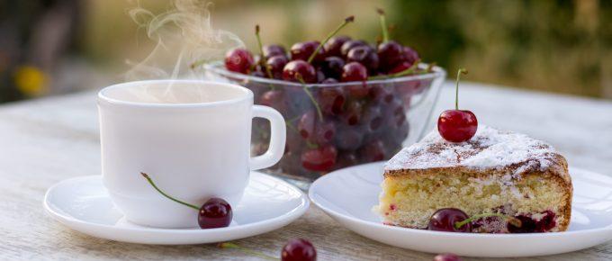 Вкусный кусок вишневого пирога на белой тарелке и белая чашка горячего чая с лимоном